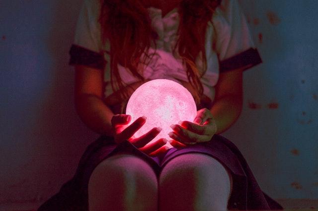 Žena drží v rukách červenú svietiacu guľu
