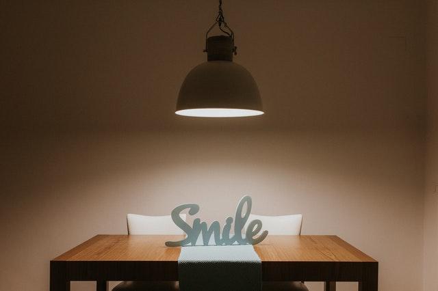 Lampa nad stolom, kde je položený nápis Smile